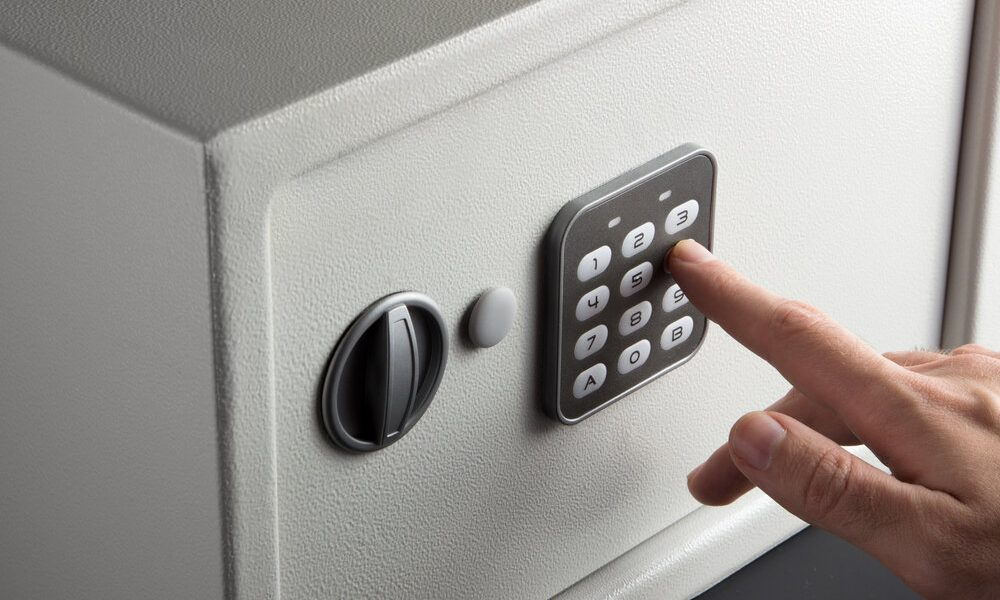 the hand opens a combination lock on the safe, a light safe on a dark background